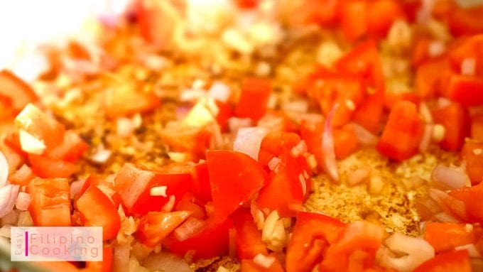 Image of garlic, onions and tomatoes being sauteed in a pan
