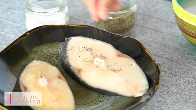 Image of raw fish being seasoned with salt and pepper