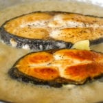 Image of golden brown fish placed in boiling sauce